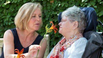 Dame houdt bloem onder neus andere dame in rolstoel