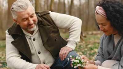 Een man en een vrouw plukklen bloemen in een veld