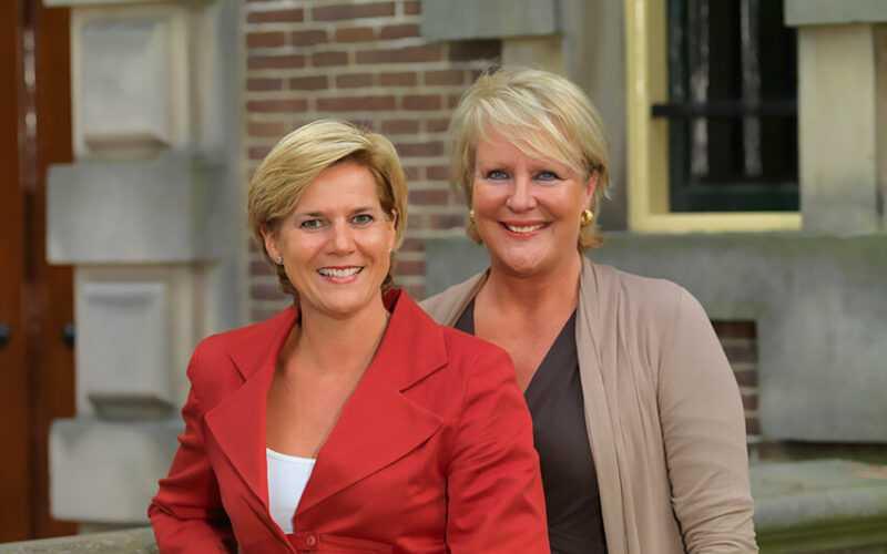 Twee keurig verzorgde dames met op de achtergrond de gevel van een gebouw