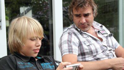 Jongen spelend op telefoon , man ernaast kijkt toe