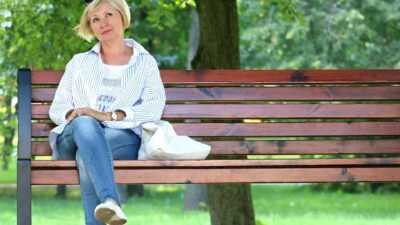 Mevrouw alleen op bankje in park, even genietend van rust