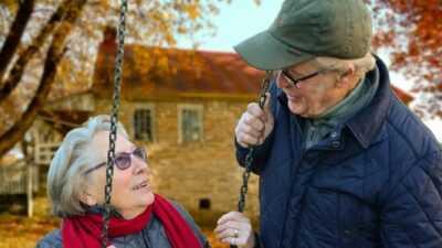 Een oudere vrouw en man bij schommel, de vrouw zit op de schommel