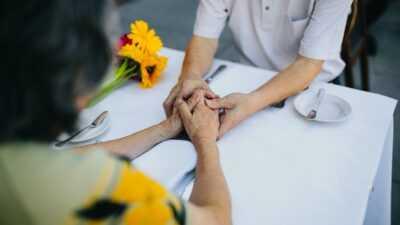 Een gedekte tafel met daaraan vrouw en man die elkaars handen vasthouden