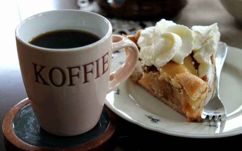 Een beker met de naam koffie erop met daarnaast appeltaart met slagroom