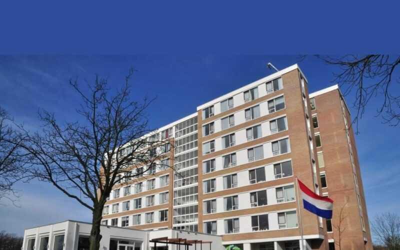 Flatgebouw Roomburg met daarvoor de Nederlandse vlagh