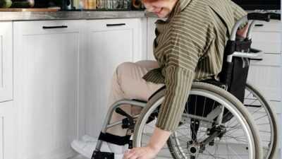 Een vrouw in rolstoel die poes aait
